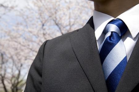 桜を背景にしている新入社員